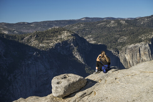 Side view of woman sitting on cliff at Yosemite National Park against blue sky - CAVF59385