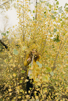 Woman standing amidst plants during autumn - CAVF59394