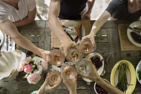 Cropped hands of friends toasting drinks at dining table - CAVF59427