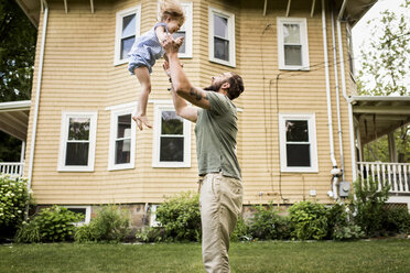 Side view of father throwing daughter while standing by house at yard - CAVF59481