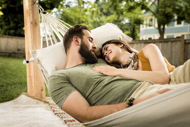 Smiling couple relaxing on hammock at yard - CAVF59484