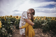 Portrait of girls embracing while standing in sunflower field against sky - CAVF59490
