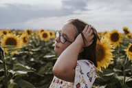 Close-up of girl with hand in hair standing in sunflower field against sky - CAVF59493