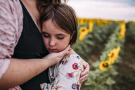 Midsection of mother embracing daughter while standing in sunflower farm - CAVF59496