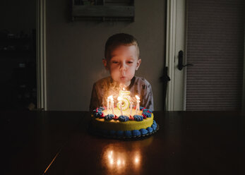 Boy blowing birthday candles on table at home - CAVF59502