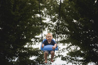 Portrait of cute baby boy swinging against trees at playground - CAVF59511