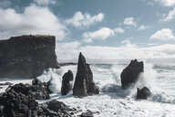Scenic view of waves splashing on rock formations in sea against cloudy sky - CAVF59520