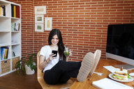 Young woman with smoothie using smart phone while resting legs on table at home - CAVF59529