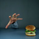 Midsection of a person reaching out for a burger on a black background. - INGF08957