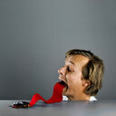 Surreal studio shot of a long human tongue catching a toy insect - INGF08984