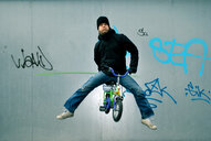 Action shot of a man riding his bicycle in mid air against a graffiti wall - INGF09029