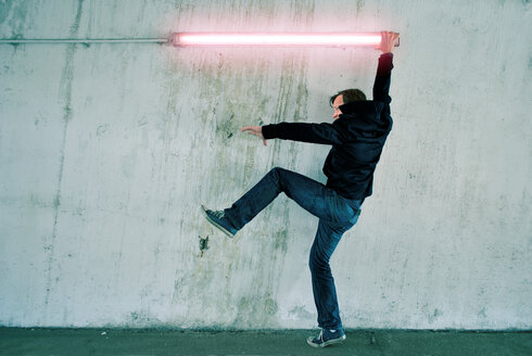 Full length of a man standing against a white wall holding onto a neon light - INGF09044
