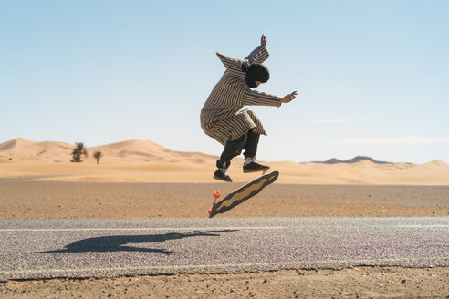 Side view of man jumping while skateboarding on road against sky - CAVF59572