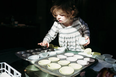 Cute girl arranging cupcake holders in baking sheet - CAVF59629
