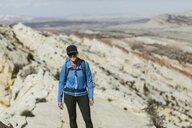 Female hiker with backpack standing on mountain during sunny day - CAVF59638