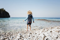 Rear view of girl standing on shore against clear sky at Bruce Peninsula National Park - CAVF59650