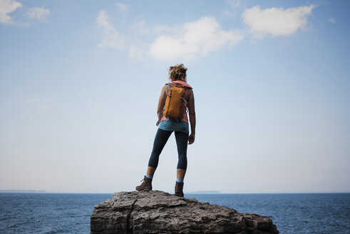 Rear view of female hiker with backpack standing on rock against sea and sky at Bruce Peninsula National Park - CAVF59653