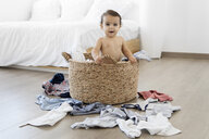 Portrait of shirtless baby girl standing in laundry basket at home - CAVF59665
