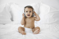 Happy shirtless baby girl with headphones sitting on bed - CAVF59668