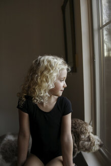 Girl with dog looking through window while sitting at home - CAVF59671