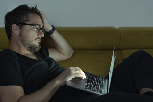 Man lying on couch using laptop at night - ERRF00296