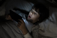 Shocked girl lying in bed using smartphone at night - ERRF00311