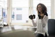 Businesswoman sitting in office, training with dumbbells - MOEF01887