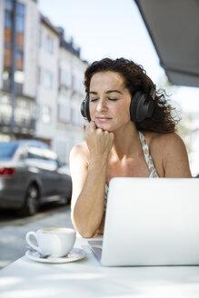 Mature woman sitzting in cafe, wearing headphones, using laptop - MOEF01896