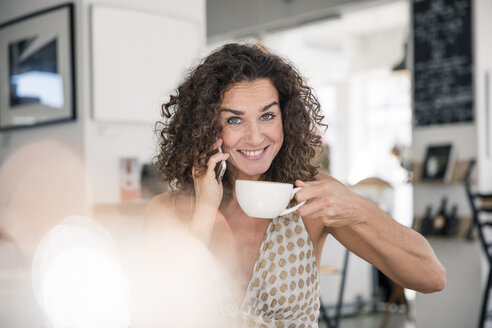 Mature woman sitting in coffee shop, talking on the phone, drinking coffee - MOEF01926