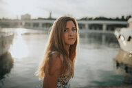 Portrait of a beautiful young woman with long brown hair standing by the water - INGF09338