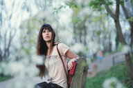 Portrait of a beautiful young woman sitting outdoors - INGF09425