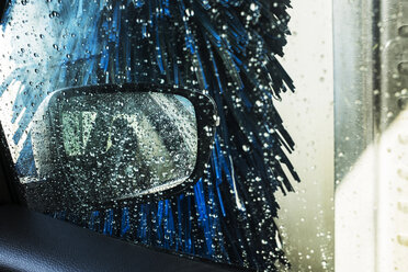 View from the inside of a car in an automated car wash, blue washers and soapy water over the windows. - MINF09716