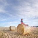 Young woman sitting on hay bales in field. - INGF09659