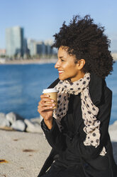 Spain, Barcelona, smiling woman sitting on a wall with coffee to go - AFVF02070