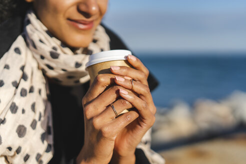 Woman's hands holding coffee to go, close-up - AFVF02073