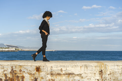 Spain, Barcelona, laughing woman dressed in black walking on wall at sunlight - AFVF02079