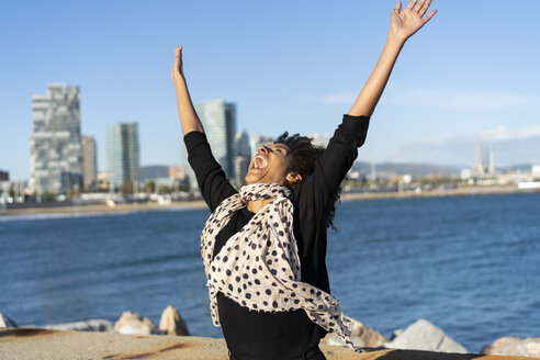 Spain, Barcelona, happy woman shouting of joy in front of the sea - AFVF02082