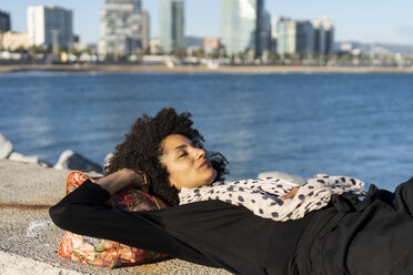 Spain, Barcelona, woman dressed in black relaxing on a wall at sunlight - AFVF02085