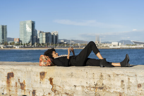 Spain, Barcelona, woman dressed in black lying on a wall in front of the sea using smartphone - AFVF02088