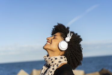 Smiling woman listening music with white headphones near the sea - AFVF02103