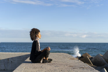 Woman sitting on wall in front of the sea meditating - AFVF02106
