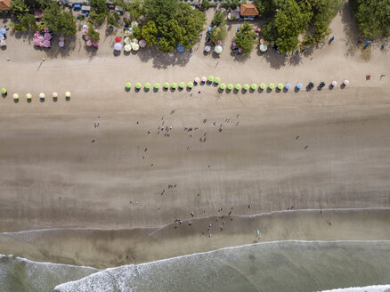 Bali, Kuta Beach, row of beach umbrellas and people on the beach, aerial view - KNTF02508