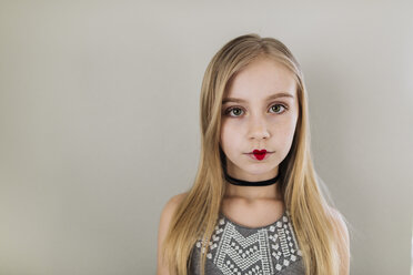 Portrait of girl with heart shape lipstick standing against wall - CAVF59680