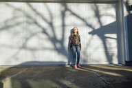 Full length of girl looking away while standing by wall - CAVF59686