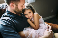 Portrait of girl with father sitting on sofa at home - CAVF59701