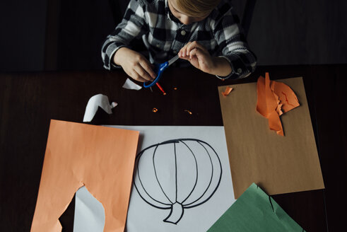 High angle view of boy holding scissor while making pumpkin craft at table - CAVF59734