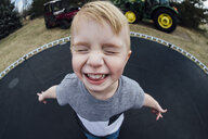 High angle view of cheerful boy playing on trampoline - CAVF59809