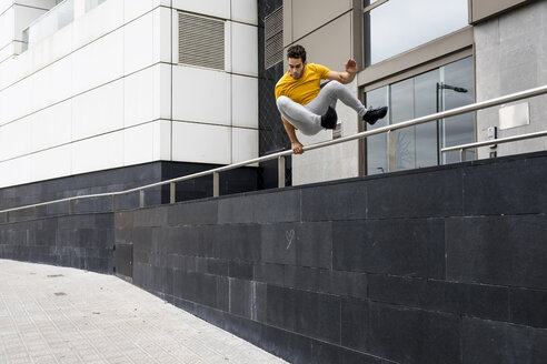 Young man jumping over railing - MAUF01869