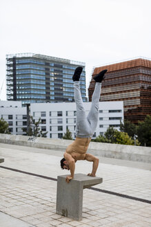 Young man during workout, handstand on bench - MAUF01896