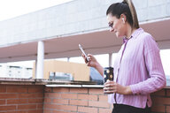 Woman holding coffee mug, using smartphone - ERRF00334